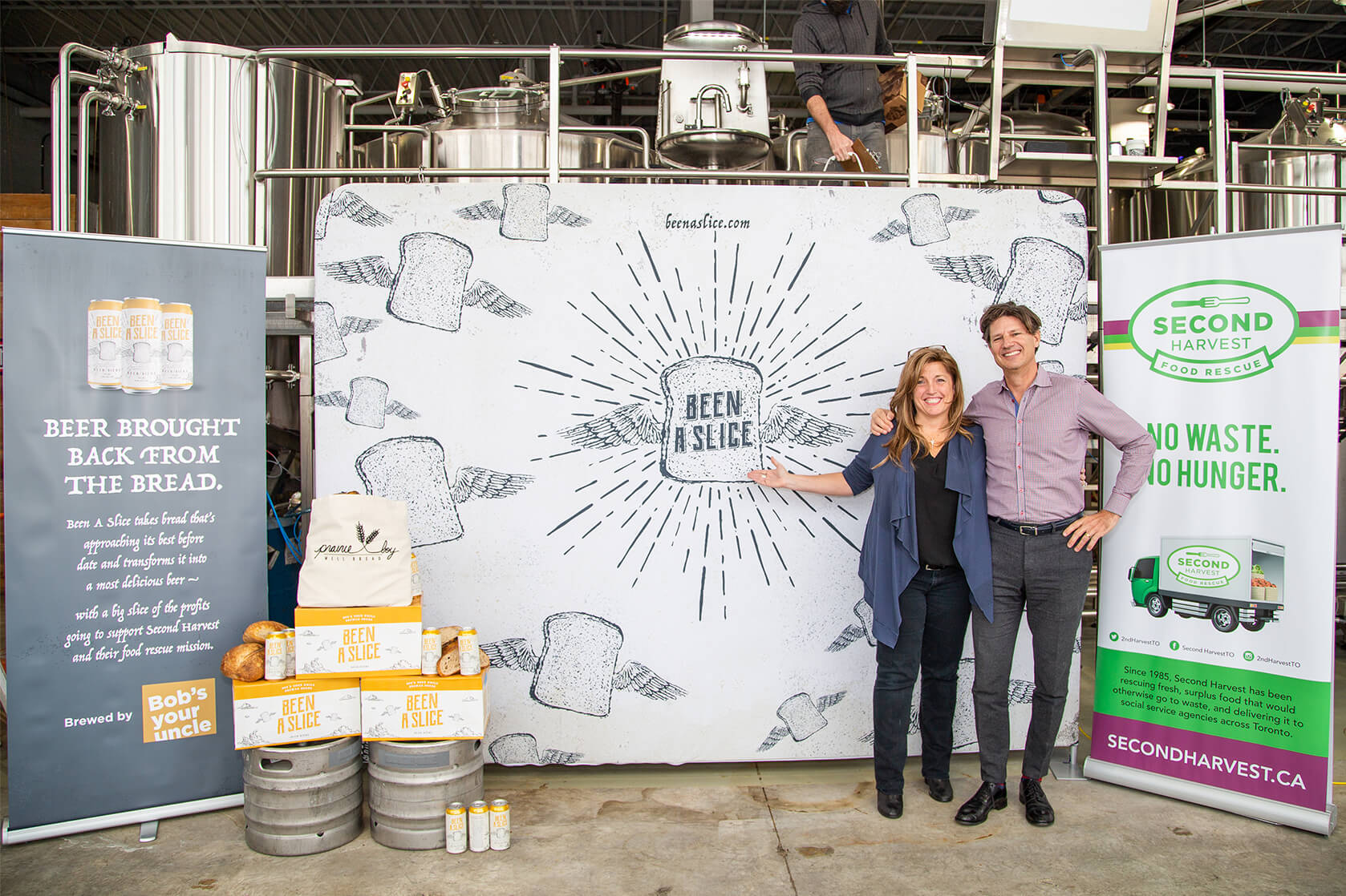Bob Froese of Bob's Your Uncle and Lori Nikkel of Second Harvest posing in front of a Been A Slice banner at Common Good Brewing Company.